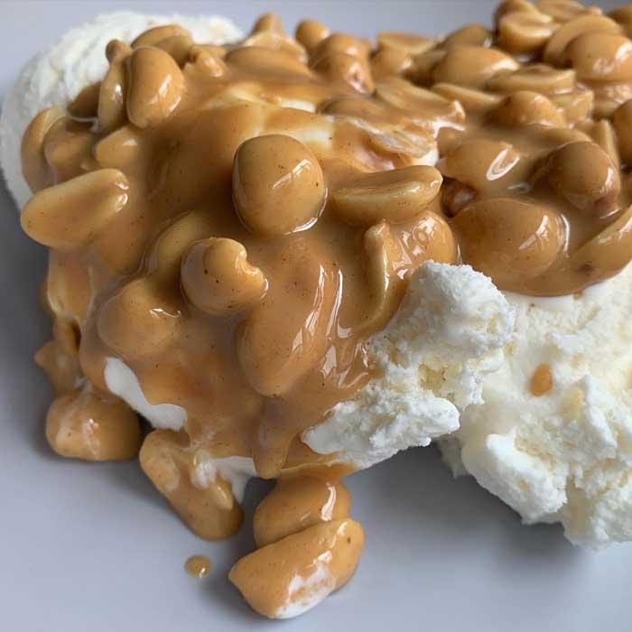Warm peanut sauce on vanilla ice cream